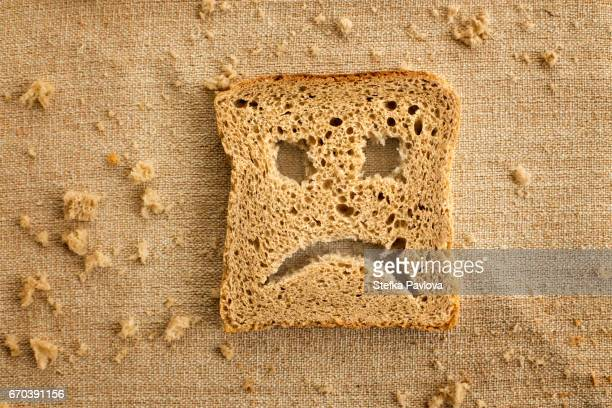 A slice of bread toast with a sad face