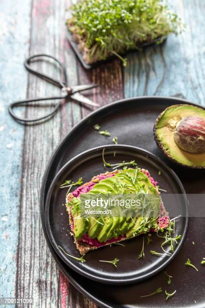 Slice of bread with beetroot hummus, slices of avocado and cress