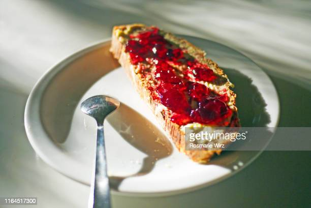 a slice of bread with butter and red jam - preserves stock pictures, royalty-free photos & images