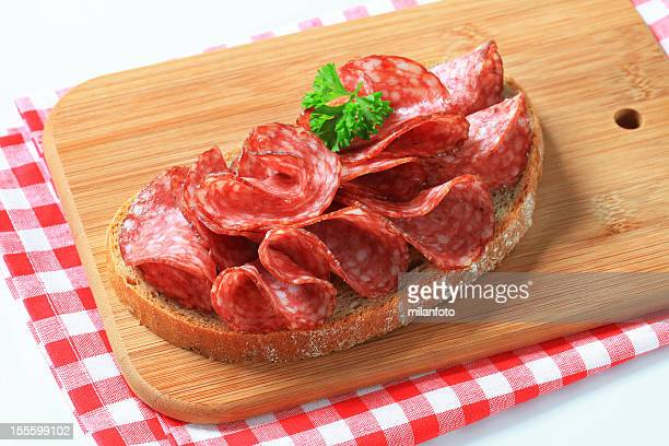 Slice of bread with Hungarian salami on a cutting board