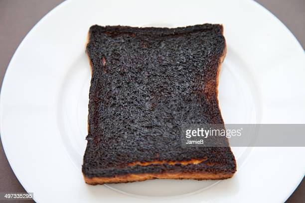 slice of burnt toast on a plate - failure stock photos and pictures