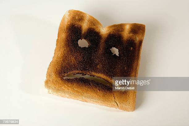 A slice of burnt toast with a sad face