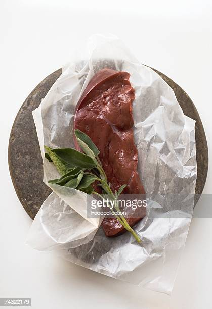 A slice of calf's liver with sage on paper