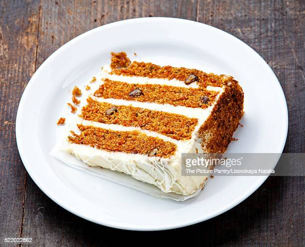 Slice of carrot cake on wooden background