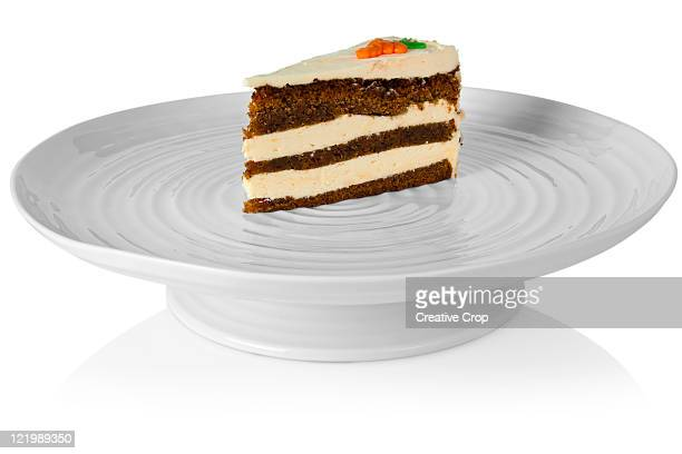 Slice of carrott cake sat on a porcelain cake stan