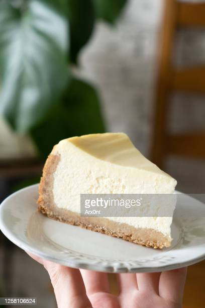 slice of cheesecak on plate in hands - チーズケーキ ストックフォトと画像