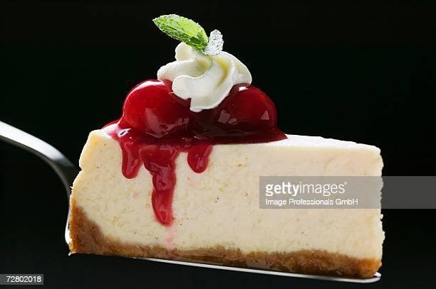 Slice of cheesecake with cherries, cream, mint on cake server