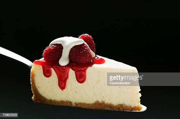 Slice of cheesecake with raspberries & cream on cake server