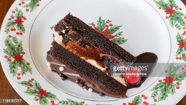 Slice of chocolate cake served in a plate with Christmas decorations Cakes are very popular during the festive season