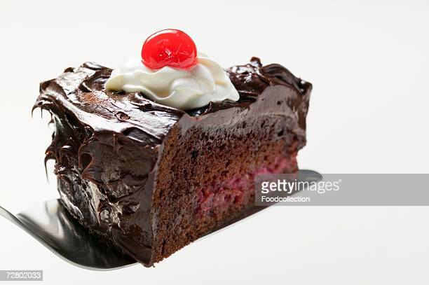 Slice of chocolate cake with cream & cherry on cake server