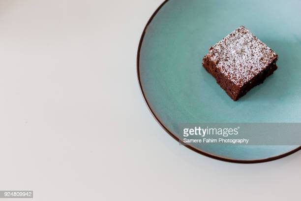 slice of chocolate cake with powdered sugar on plate - samere fahim stock photos and pictures