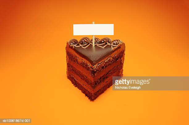 Slice of chocolate cake with small blank sign, orange background
