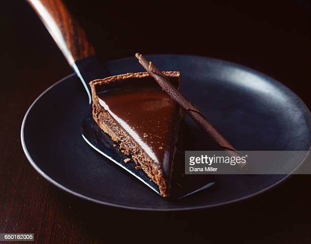 Slice of chocolate with cake server on plate