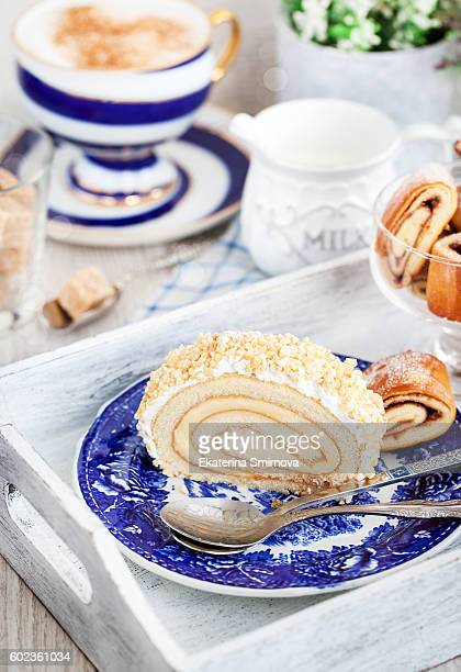 Slice of delicious sponge cake roll and cup of coffee