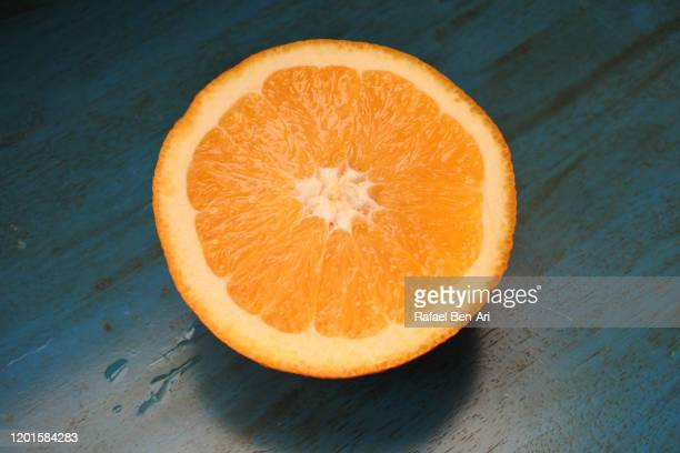 slice of fresh orange fruit on green wooen table - rafael ben ari stock pictures, royalty-free photos & images