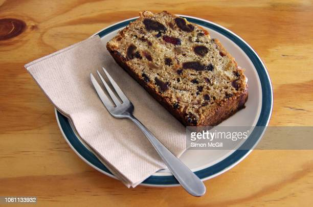 slice of fruit and nut loaf cake on a plate with a cake fork and paper napkin - fruit cake stock pictures, royalty-free photos & images
