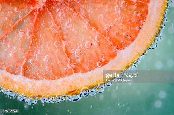 slice of grapefruit in beverage - zitrusfrucht stock-fotos und bilder
