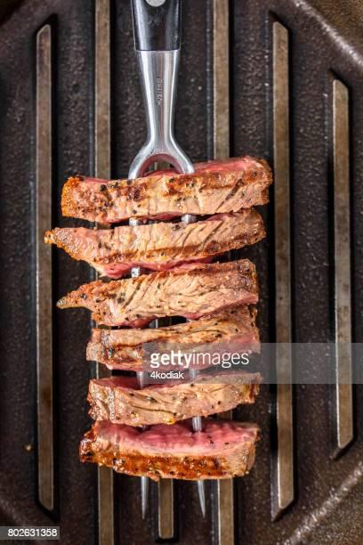 フォークと鋳鉄製のグリルに調味料とステーキのスライス