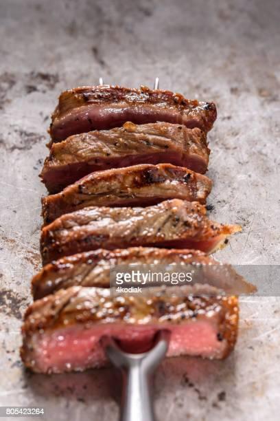 フォークに調味料とステーキのスライス