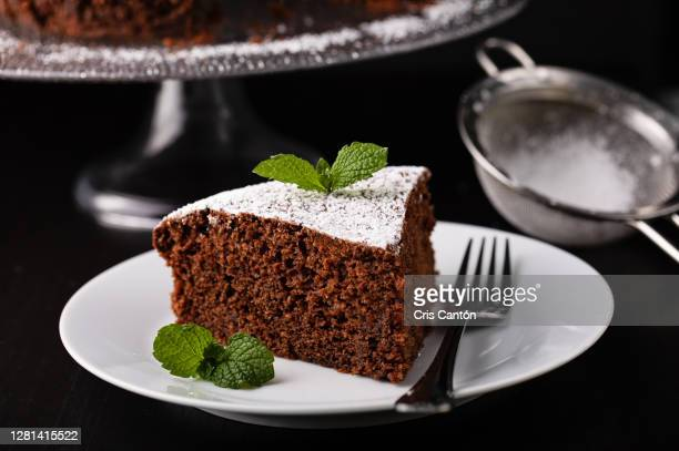slice of homemade chocolate cake with icing sugar - cris cantón photography fotografías e imágenes de stock
