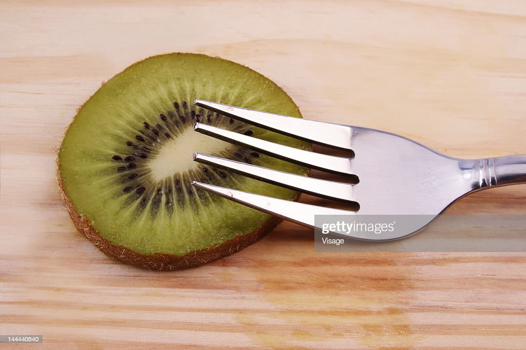 Slice of kiwifruit and a fork : Stock Photo