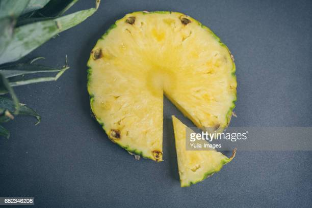 Slice of pineapple and crown of leaves