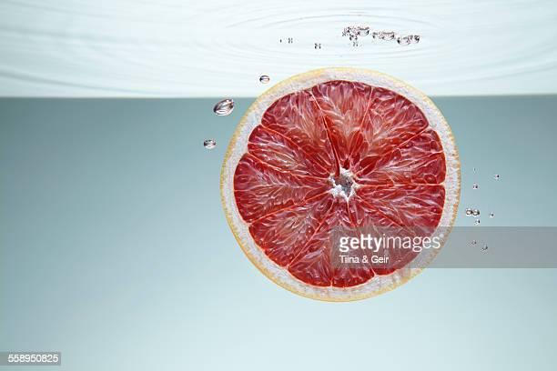 Slice of pink grapefruit underwater