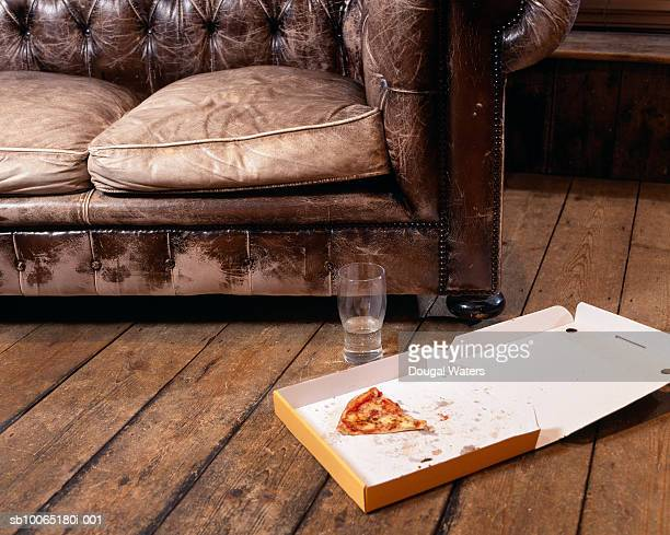 Slice of pizza in box on floor in living room