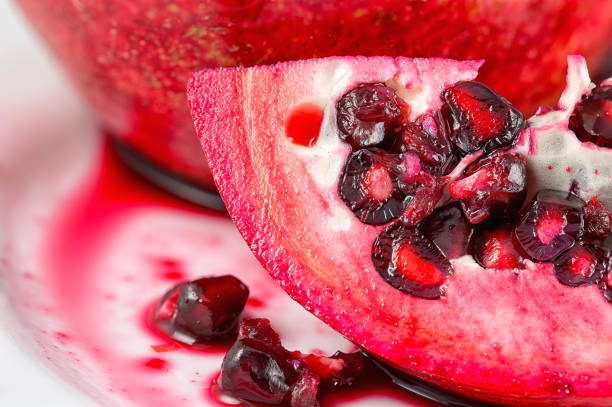 a slice of pomegranate - pomegranate tree stock photos and pictures