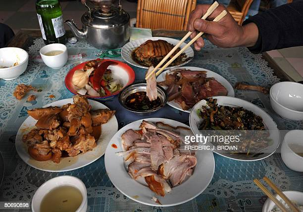 A slice of pork is placed into a dipping sauce on a table full of pork dishes on March 23 2008 on the outskirts of Lijiang in southwest China's...