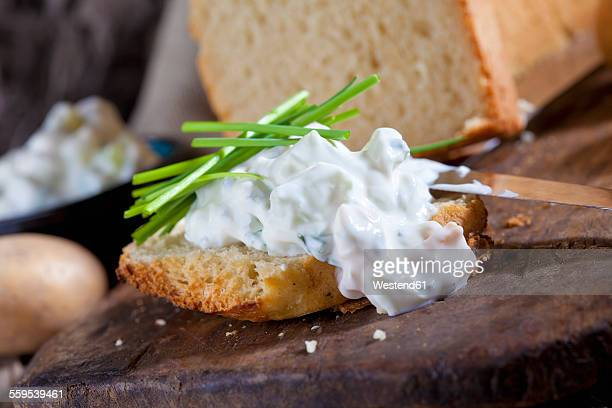 Slice of potato bread spread with herbed curd cheese garnished with chives