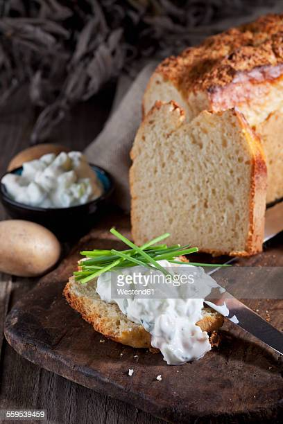 Slice of potato bread spread with herbed curd cheese