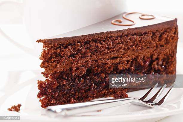Slice of Sacher cake in plate with coffee cup in background