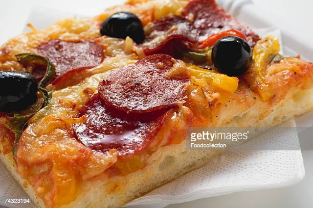 a slice of salami pizza with peppers and olives - olive pimento stock photos and pictures