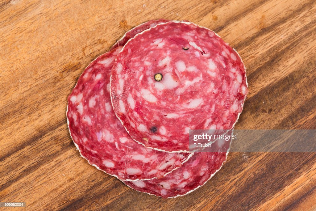 Slice of salami sausages on wooden board isolated : Stock-Foto