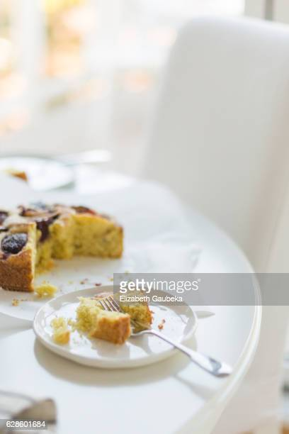 A slice of stone fruit cake on white round table