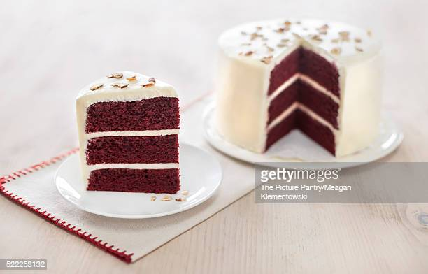 Slice of three layered red velvet cake with whole cake in backgr