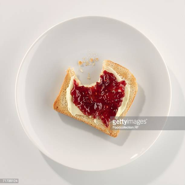 A slice of toast with butter and jam, a bite taken