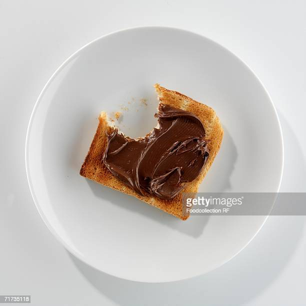 A slice of toast with Nutella, a bite taken, on a plate