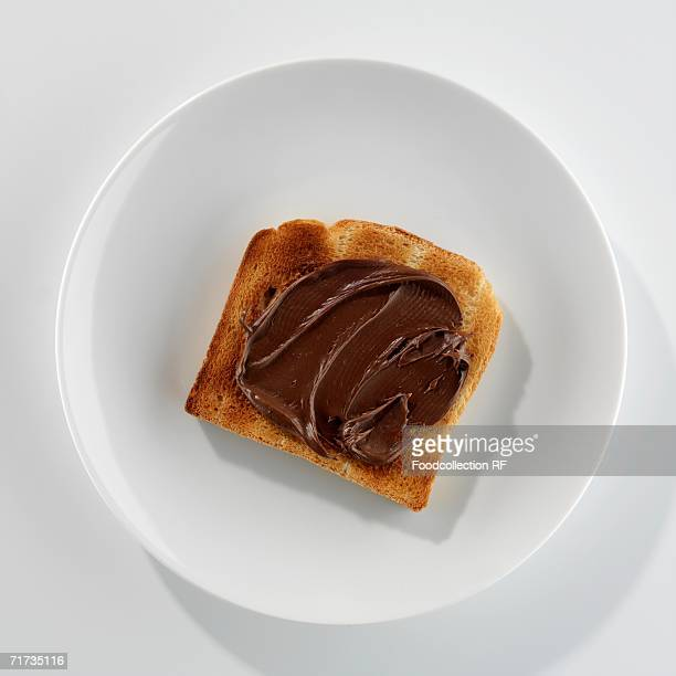 a slice of toast with nutella on a plate - nutella stock pictures, royalty-free photos & images