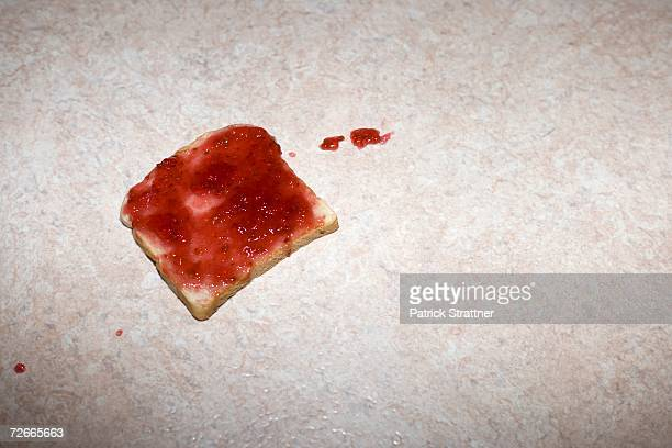 slice of toast with strawberry jam dropped on the floor - lino stock pictures, royalty-free photos & images