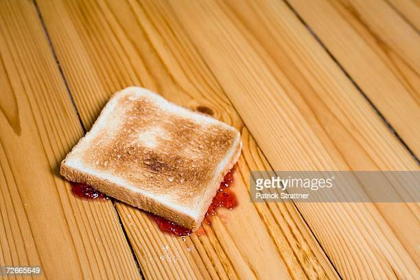 Slice of toast with strawberry jam turned upside down on floor