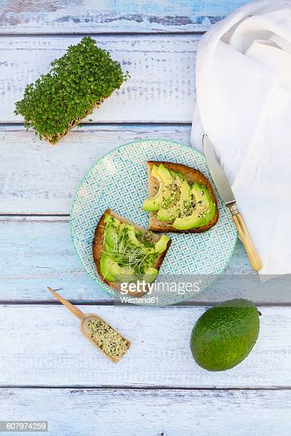 Slice of toasted bread with acocado, cress and hemp seeds on a plate