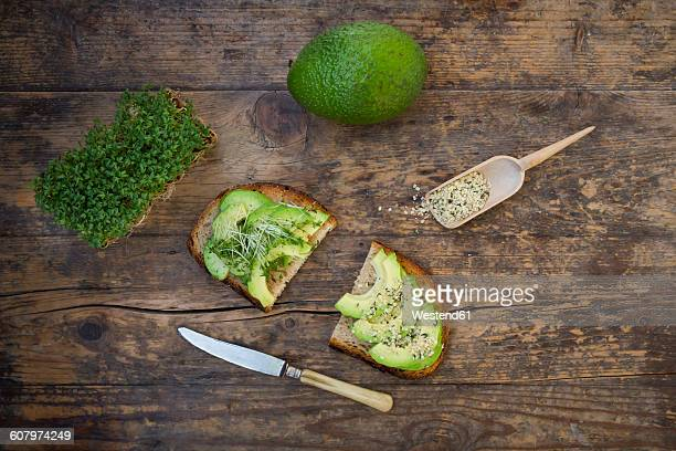 Slice of toasted bread with acocado, cress and hemp seeds on wood