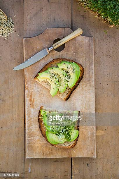 Slice of toasted bread with acocado, cress and hemp seeds on wooden board