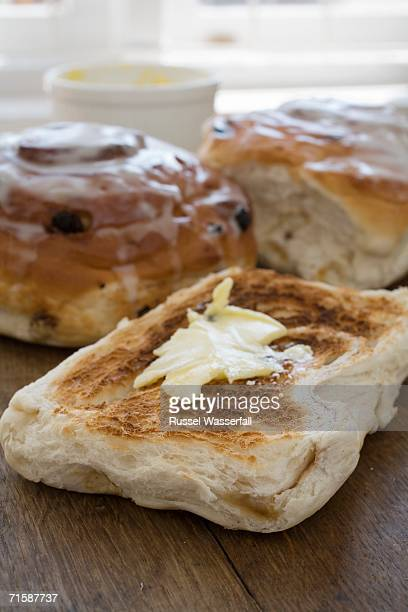 Slice of Toasted Bread with Melting Butter and Chelsea Buns in the Background