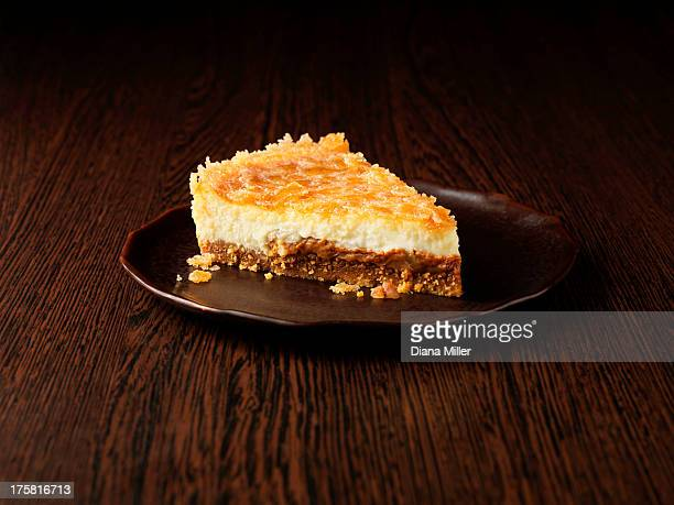 Slice of toffee and pecan cheesecake on dark brown plate on dark wooden surface