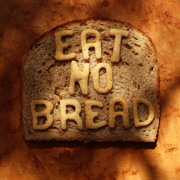"""A slice of wheat bread with the words """"EAT NO BREAD"""" made from baked wholewheat dough letters placed on it - part of a series"""