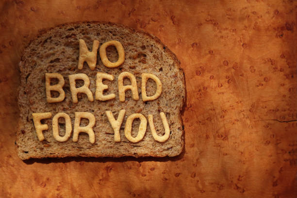 """A slice of wheat bread with the words """"NO BREAD FOR YOU"""" (dieting concept) made from baked dough letters placed on it - part of a series"""