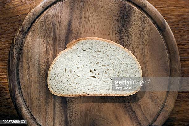 Slice of white bread on wooden chopping board
